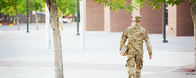 Military man walking with books.